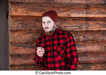Handsome man smoking on wooden background