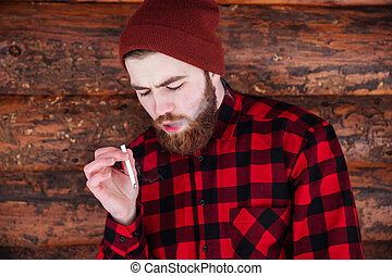 Man smoking cigarette on wooden background