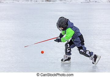 Little boy skating and playing hockey