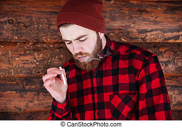 Man hipster smoking on wooden background