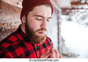 Man smoking cigarette outdoors - Hipster man smoking...