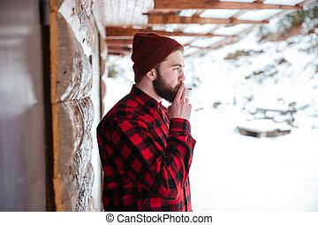 Man smoking cigarette outdoors - Man in shirt smoking...