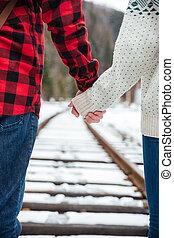 Couple walking on railway - Cropped image of couple walking...