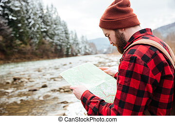 Male hiker reading map outdoors