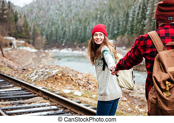 Happy young couple holding hands and walking along railway