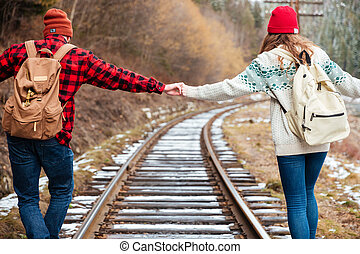 Beautiful young couple holding hands and walking along...