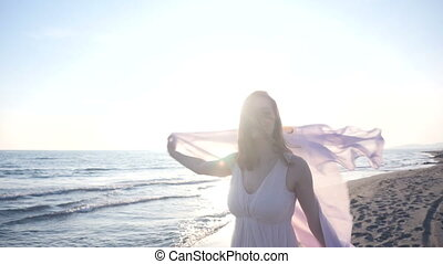 Beautiful woman holding light fabric on the beach and enjoy...
