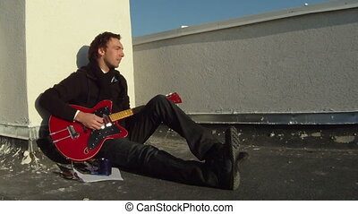A man sitting on the floor playing the guitar singing a...