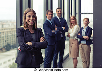 Corporate portrait of young business woman with her colleagues in background.
