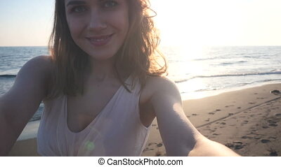 beautiful woman taking selfie using phone on beach at sunset...
