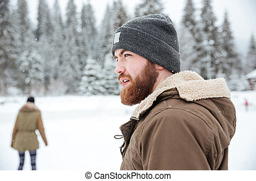 Portrait of a man looking away outdoors with snow on...