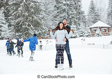 Smiling couple in ice skates hugging outdoors with snow on...