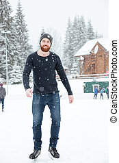 Handsome man ice skating outdoors - Full length portrait of...