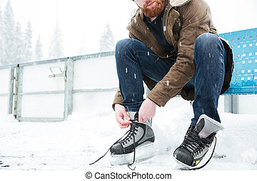 Man tying shoelace on ice skates outdoors - Cropped image of...