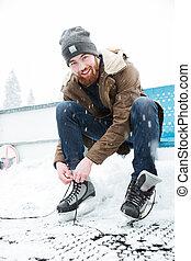 Man tying shoelace on ice skates outdoors - Happy man tying...