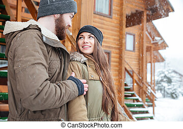 Couple standing and looking at each other in winter -...