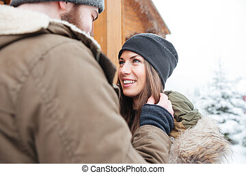Couple standing outdoors together in winter - Loving...