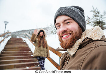 Smiling bearded man walking with his girlfriend in winter...