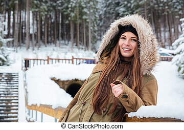 smiling beautiful young woman with long hair in winter forest
