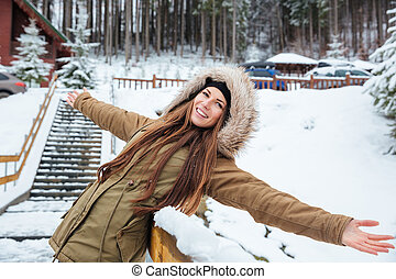 Happy attractive young woman standing and relaxing near the...