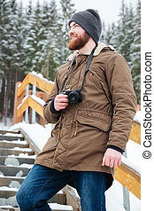 Smiling bearded man taking pictures in winter forest -...