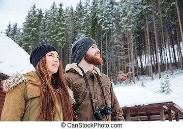 Beautiful young couple standing and enjoying winter forest -...