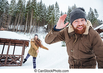 Couple playing snowballs in winter forest - Happy young...