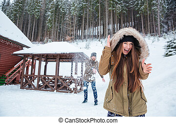 Happy excited young couple playing snowballs in winter forest
