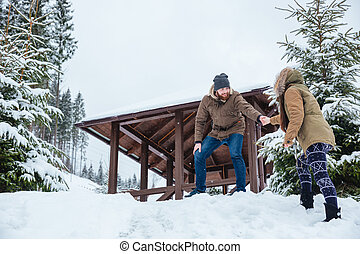 Man helping his girlfriend on walk mountains in winter -...