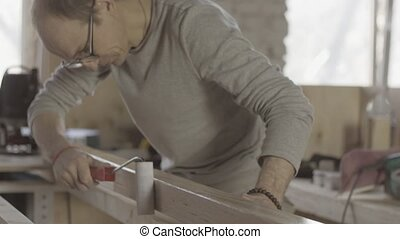 Carpenter varnishing long wooden board by paint roller...