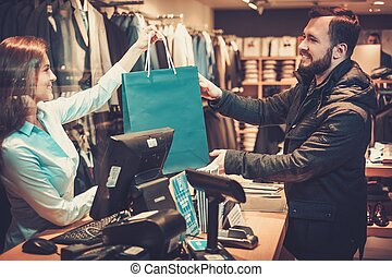 Happy handsome man taking shopping bag from saleswoman in a...