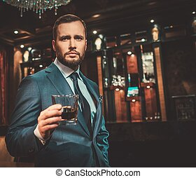 Confident well-dressed man with glass of whisky in luxury...