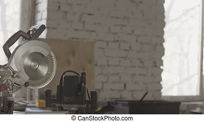 View of adult carpenter stay with glasses in hands. Thinking. Circular saw