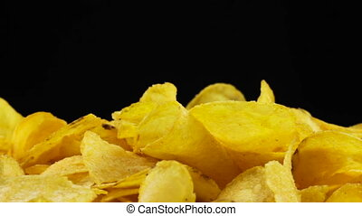 Potato Chips Rotating on Black Background - Potato chips are...