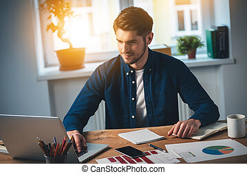 Surfing net at work Cheerful young handsome man looking at...
