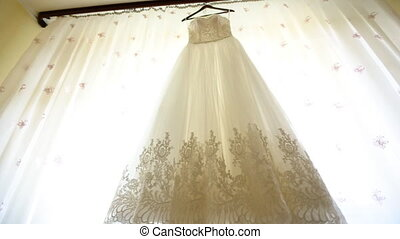 Close up of a fashionable wedding dress on a hanger , white shoes on the floor and a  bouquet with pink roses in the room of the bride.