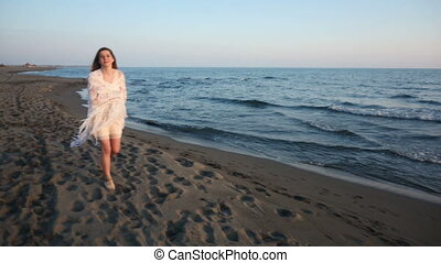 beautiful young woman walking on the beach towards, turns...