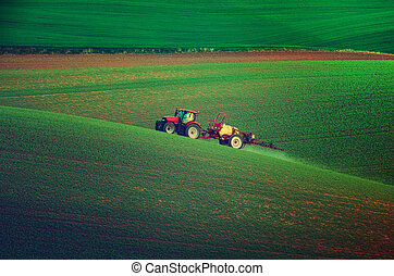 Farm machinery spraying insecticide to the green field,...
