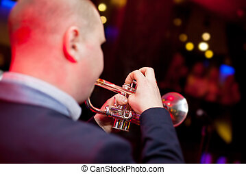 Trumpeter plays the trumpet in a nightclub.