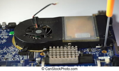 man repair laptop motherboard with screwdriver. remove...