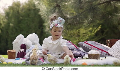 Happy child sits on a meadow around Easter decoration - Cute...