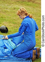 The girl-parachutist in blue overalls