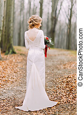 Beautiful blonde bride in long lace wedding dress at the...