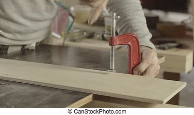Professional carpenter fixing one wooden board on another. Making furniture