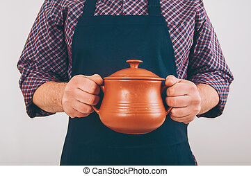 Cook man with big pot isolated on white background