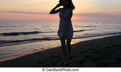 beautiful young woman enjoying the sunset on the beach