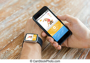 close up of hands with smart phone and watch - sport,...