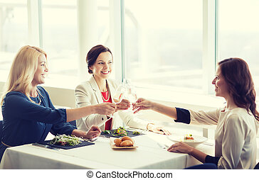 happy women drinking champagne at restaurant - people,...