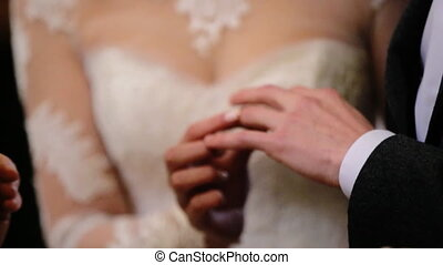 Lovely beautiful  bride wearing fashionable white wedding dress  put gold ring on a finger of a young groom in  black suit.