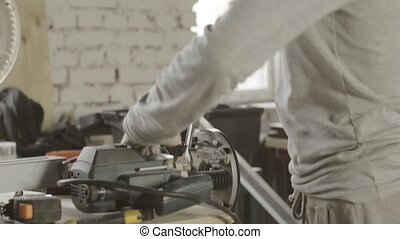 Professional woodworker adjusts special polishing machine by wrench. Furniture